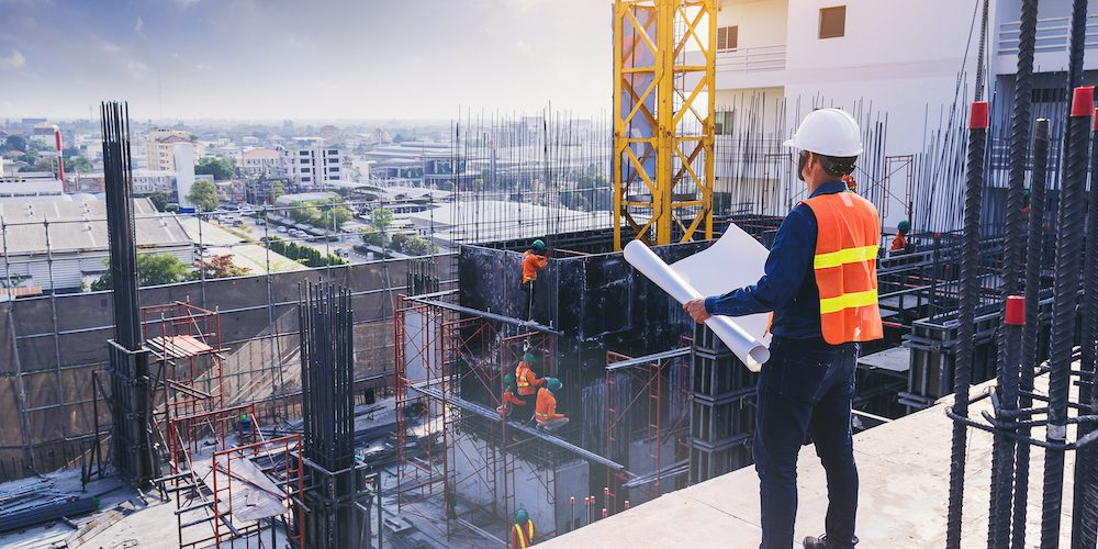 Smart civil architect engineer inspecting and working outdoors building side with blueprints. engineering and architecture concept.